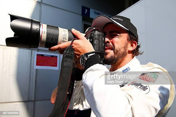 Fernando Alonso of Spain and McLaren Honda takes a photograph of the photographers after posing for them outside the team garage during previews to...
