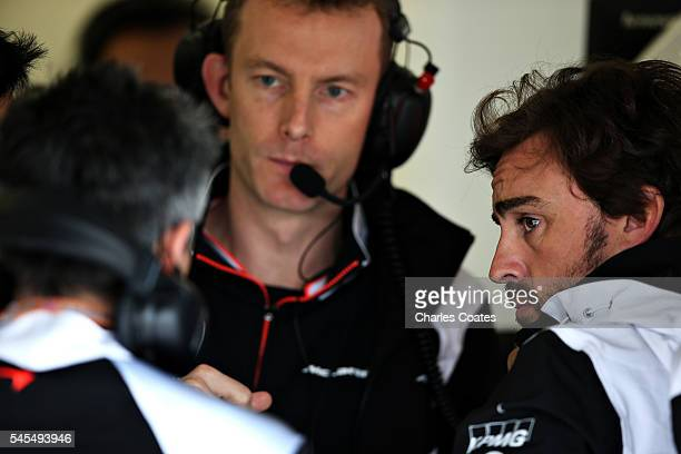 Fernando Alonso of Spain and McLaren Honda talks to his engineers in the garage during practice for the Formula One Grand Prix of Great Britain at...