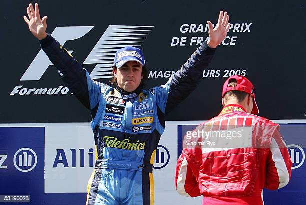 Fernando Alonso of Spain and Renault celebrate his victory and Michael Schumacher of Germany and Ferrari steps on the podium as 3rd after the French...