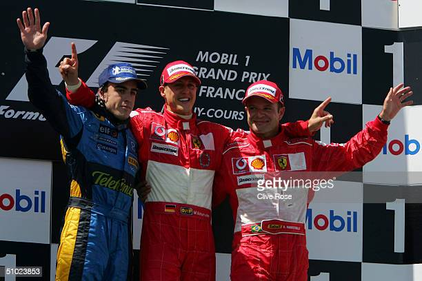 Fernando Alonso of Spain and Renault celebrates with Michael Schumacher and Rubens Barrichello on the podium after the French F1 Grand Prix at the...