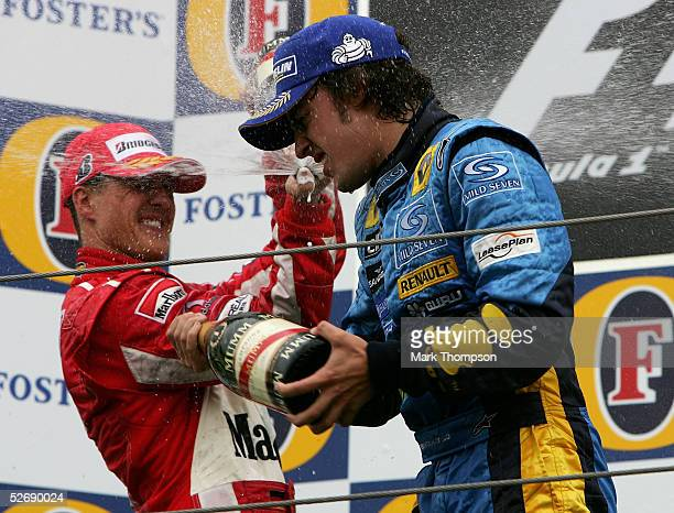 Fernando Alonso of Spain and Renault celebrates with Michael Schumacher of Germany and Ferrari after winning the San Marino F1 Grand Prix at the San...