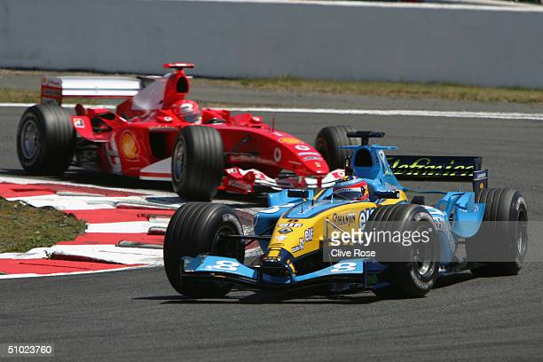Fernando Alonso of Spain and Renault holds of Michael Schumacher during the French F1 Grand Prix at the Magny-Cours Circuit on July 4 in Magny-Cours,...