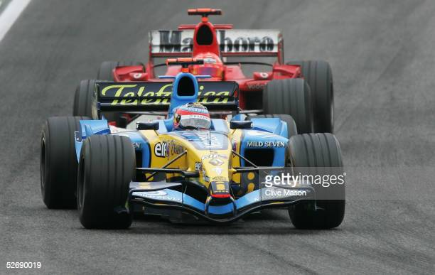 Fernando Alonso of Spain and Renault leads second placed Michael Schumacher of Germany and Ferrari during the San Marino F1 Grand Prix at the San...