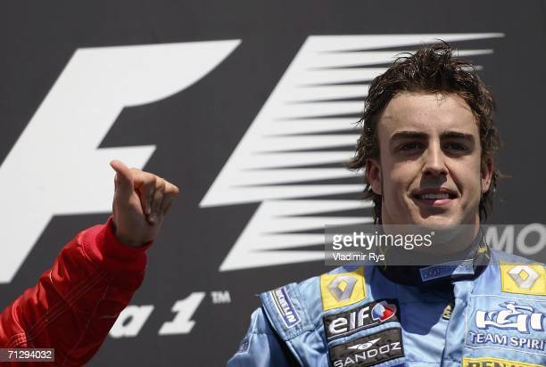 Fernando Alonso of Spain and Renault looks on during the winning ceremony after finishing first as Michael Schumacher of Germany and Ferrari cheers...