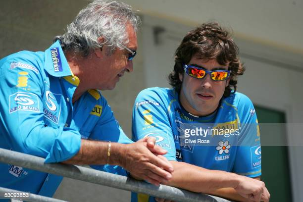 Fernando Alonso of Spain and Renault talks with Flavio Briatore in the paddock prior to the first practice session for the United States F1 Grand...