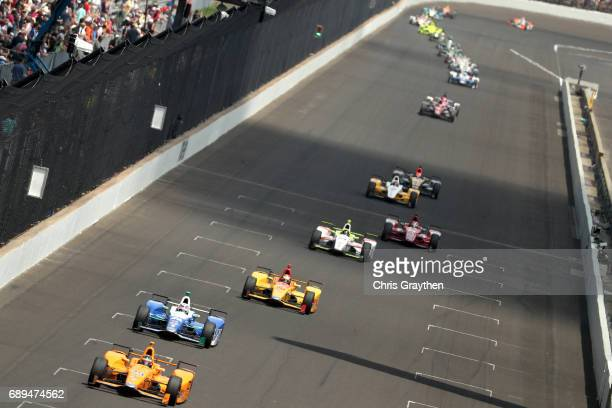 Fernando Alonso of Spain, driver of the McLaren-Honda-Andretti Honda leads a pack of cars during the 101st Indianapolis 500 at Indianapolis...