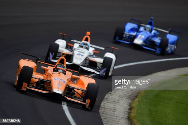 Fernando Alonso of Spain, driver of the McLaren-Honda-Andretti Honda, leads a group of cars during the 101st Indianapolis 500 at Indianapolis...