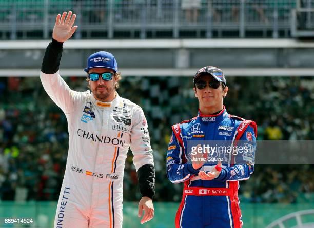 Fernando Alonso of Spain driver of the McLarenHondaAndretti Honda waves during driver introductions alongside Takuma Sato of Japan driver of the...
