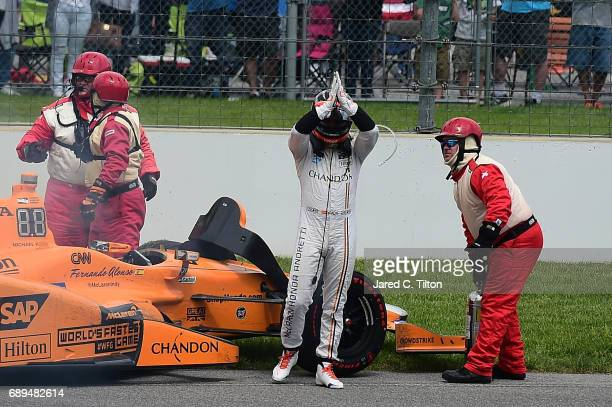 Fernando Alonso of Spain, driver of the McLaren-Honda-Andretti Honda, exits his car after his engine expired during the 101st Indianapolis 500 at...
