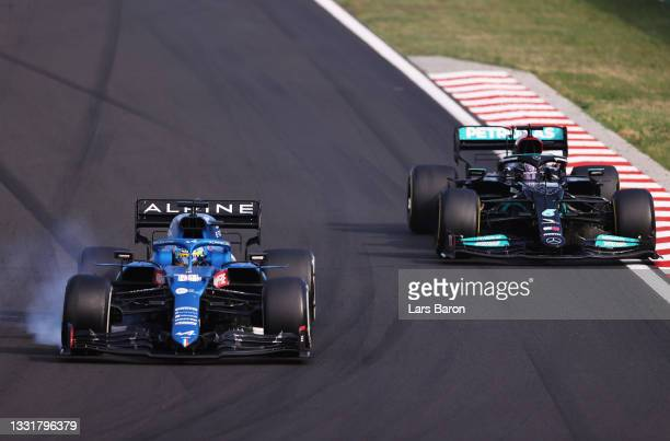 Fernando Alonso of Spain driving the Alpine A521 Renault locks a wheel under braking as he defends from Lewis Hamilton of Great Britain driving the...