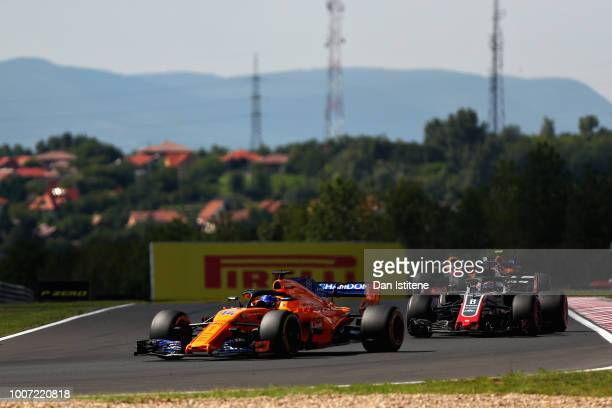 Fernando Alonso of Spain driving the McLaren F1 Team MCL33 Renault leads Romain Grosjean of France driving the Haas F1 Team VF18 Ferrari on track...