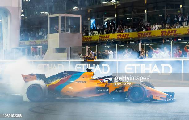 Fernando Alonso of Spain driving the McLaren F1 Team MCL33 Renault performs donuts on the pit straight during the Abu Dhabi Formula One Grand Prix at...