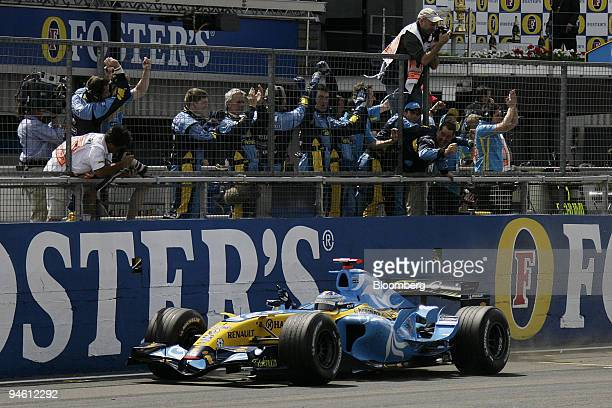 Fernando Alonso of Team Renault is seen passing his team after crossing the finish line in first place at the Formula 1 GP of Great Britain in...