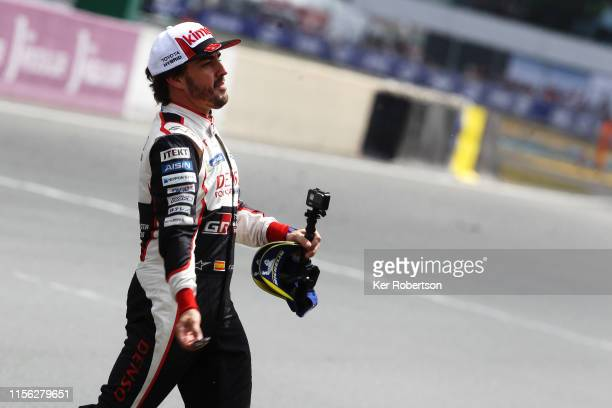 Fernando Alonso throws tyre marbles to fans as he celebrates as he and co-drivers Kazuki Nakajima and Sebastien Buemi take the flag in their Toyota...
