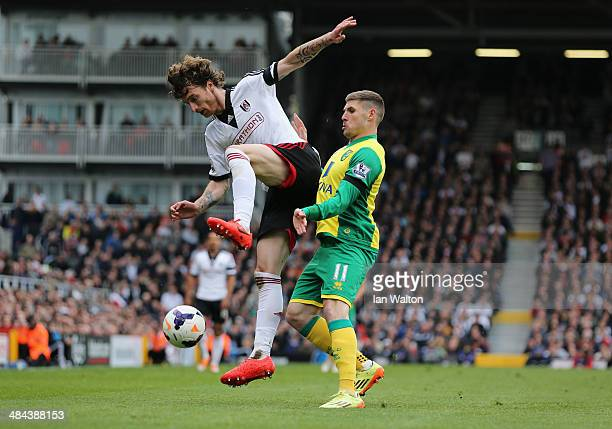 Fernando Amorebieta of Fulham beats Gary Hooper of Norwich City to the ball during the Barclays Premier League match between Fulham and Norwich City...