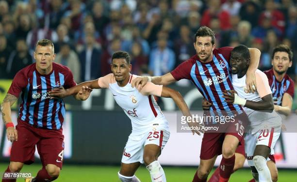 Fernando and Papa Alioune Ndiaye of Galatasaray in action against Ugur Demirok and Jan Durica of Trabzonspor during a Turkish Super Lig match between...