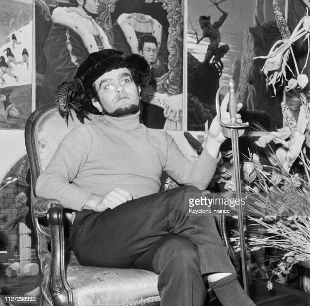 Fernando Arrabal assis dans un fauteuil coiffé de son hautdeforme et portant une épée à Paris France en 1968
