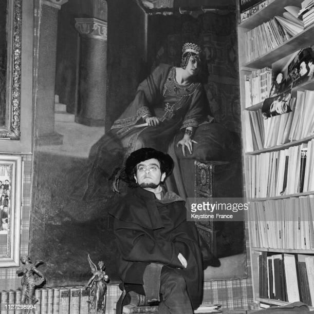 Fernando Arrabal assis sur des livres anciens prend la pose dans son appartement à Paris France en 1968