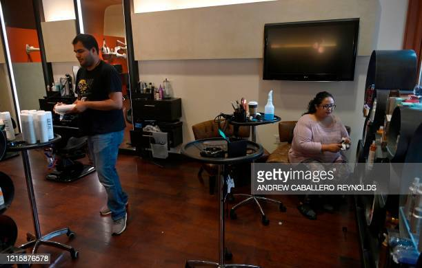 Fernando Balderas and another employee wipe down hair care products at Studio Salon and Spa a day before they reopen in Arlington Virginia on May 28...