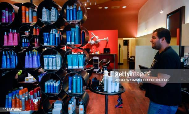 Fernando Balderas wipes down hair care products at Studio Salon and Spa a day before they reopen in Arlington Virginia on May 28 2020 Arlington...