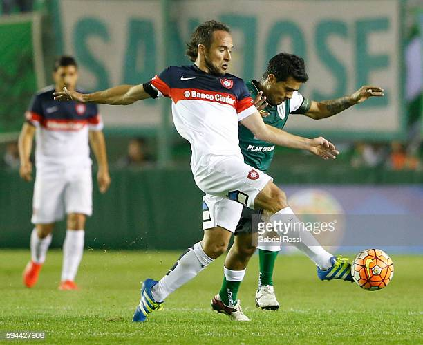 Fernando Belluschi of San Lorenzo fights for the ball with Walter Erviti of Banfield during a first leg match between Banfield and San Lorenzo as...