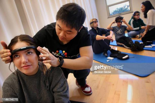 Fernando Bi of BrainCo helps sophomore Lucinda Beard left adjust her headband during a mindfulness class at the Cambridge School of Weston in Weston...