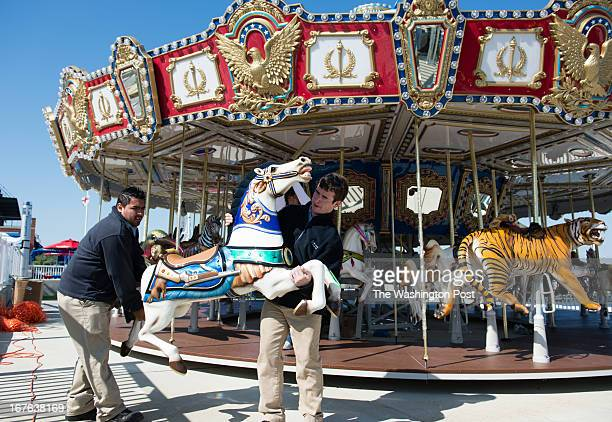 Fernando Camacho left and Brendon Ford carries a horse to be installed onto the carousel National Harbor is adding a 36foot Americanathemed carousel...