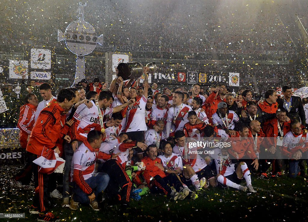 Fernando Cavenaghi of River Plate kisses teammate Leonel Vangioni as he lifts the trophy after a second leg final match between River Plate and Tigres UANL as part of Copa Bridgestone Libertadores 2015 at Antonio Vespucio Liberti Stadium on August 05, 2015 in Buenos Aires, Argentina.