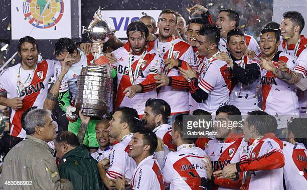 Fernando Cavenaghi of River Plate lifts the trophy as he celebrates with his teammate after winning a final match between River Plate and Tigres UANL...