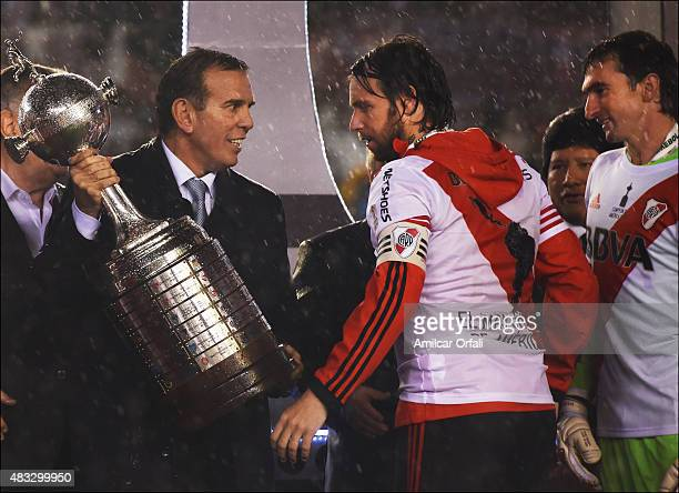 Fernando Cavenaghi of River Plate receives the trophy from Carlos Naput after winning a second leg final match between River Plate and Tigres UANL as...