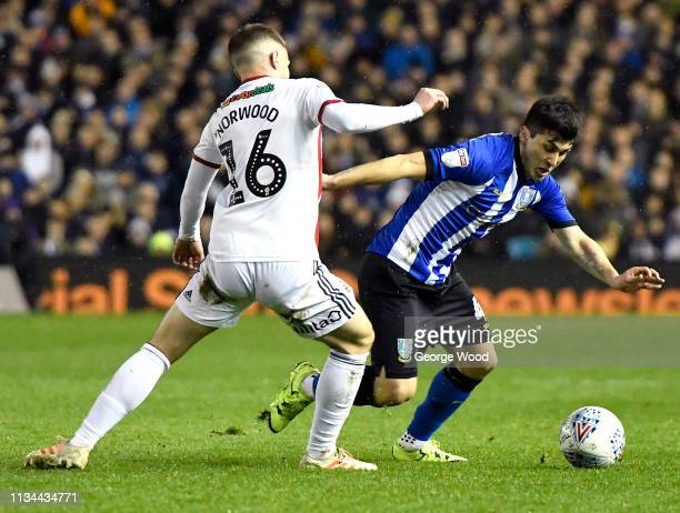 Fernando Forestieri of Sheffield Wednesday is challenged by Oliver Norwood of Sheffield United during the Sky Bet Championship match between...