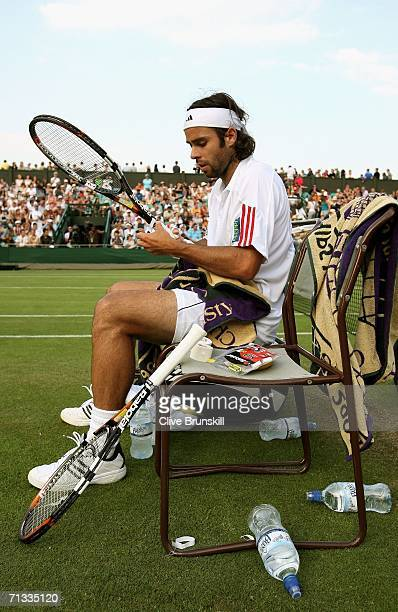 Fernando Gonzalez of Chile makes some adjustments to his racquet during between games against Marat Safin of Russia during day four of the Wimbledon...