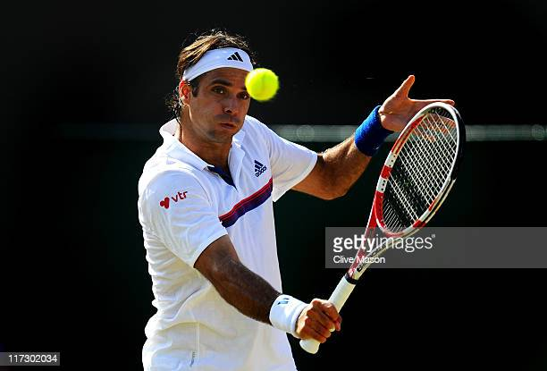 Fernando Gonzalez of Chile returns a shot during his third round match against JoWilfried Tsonga of France on Day Six of the Wimbledon Lawn Tennis...
