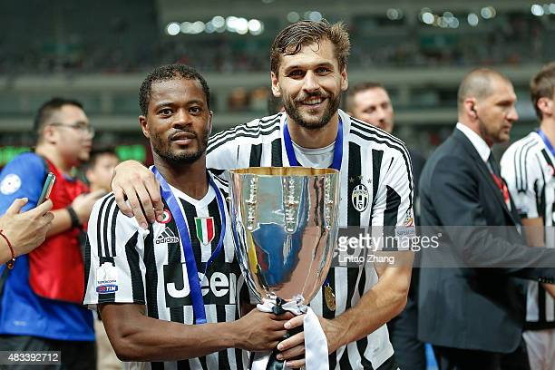 Fernando Llorente and Patrice Evra of Juventus celebrates with the trophy after winning the Italian Super Cup final football match between Juventus...
