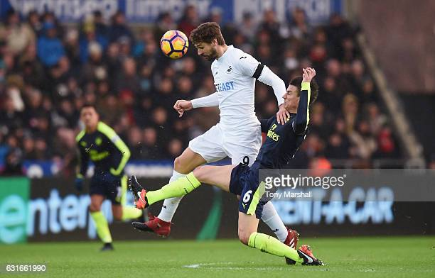 Fernando Llorente of Swansea City heads the ball while Laurent Koscielny of Arsenal attempts to tackle him during the Premier League match between...