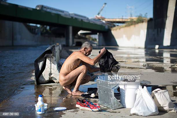 Fernando Lopez bathes and does laundry in the Los Angeles River on November 20 2015 in Los Angeles California With the approach of devastating winter...