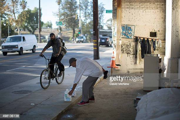 Fernando Lopez performs housekeeping chores at his street side encampment which is protected from minor storms by an overpass on November 20 2015 in...