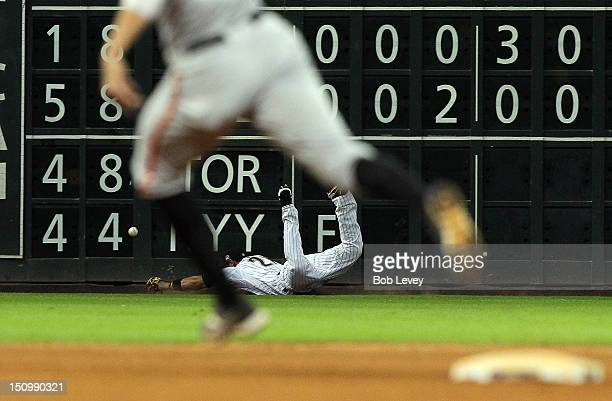 Fernando Martinez of the Houston Astros dives but can't make a catch on a ball hit by Joaquin Arias of the San Francisco Giants for a triple as...