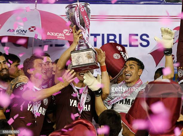 Fernando Monetti and Agustin Pelletieri of Lanus celebrate with the trophy after a final match between San Lorenzo and Lanus as part of Torneo...