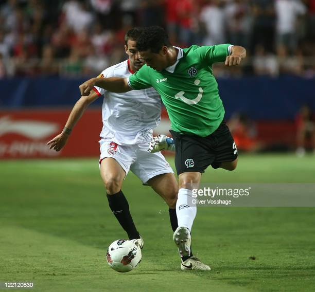 Fernando Navarro of FC Sevilla and Manuel Schmiedebach of Hannover 96 battle for the ball during the UEFA Europa League PlayOff second leg match...