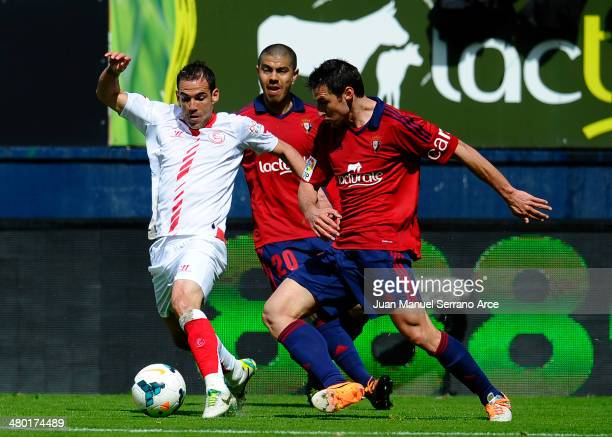 Fernando Navarro of Sevilla FC duels for the ball with Marc Bertran of CA Osasuna during the La Liga match between CA Osasuna and Sevilla FC at...