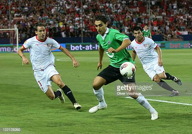Fernando Navarro of Sevilla Mohammed Abdellaoue of Hannover and Alvaro Negredo of Sevilla battle for the ball during the UEFA Europa League PlayOff...