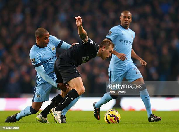 Fernando of Manchester City and Scott Arfield of Burnley battle for the ball during the Barclays Premier League match between Manchester City and...