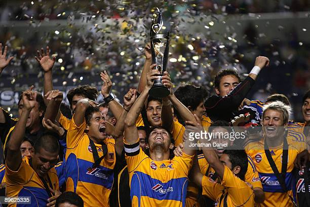 Fernando Ortiz of Tigres UANL holds the trophy as his teammates celebrate winning the SuperLiga 2009 Final over the Chicago Fire on August 5, 2009 at...