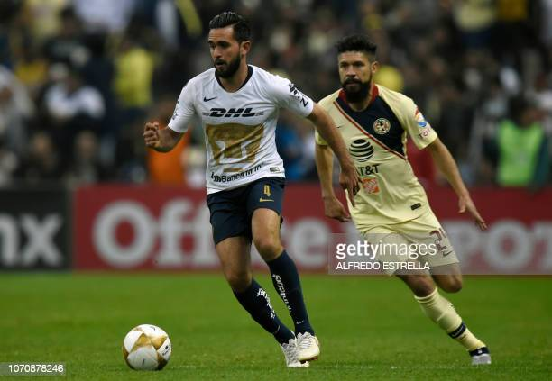 Fernando Quintana of Pumas vies for the ball with Oribe Peralta of America during the second round of semifinals of the Mexican Apertura tournament...
