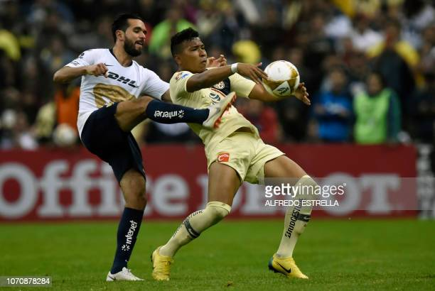 Fernando Quintana of Pumas vies for the ball with Roger Beyker Martinez of America during the second round of semifinals of the Mexican Apertura...