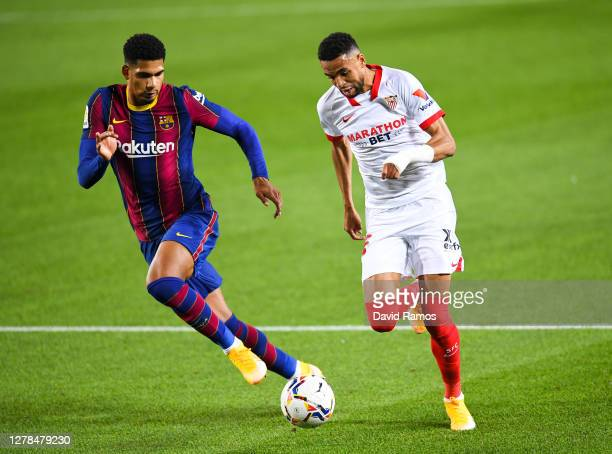 Fernando Reges of Sevilla FC competes for the ball with Ronald Araujo of FC Barcelona during the La Liga Santander match between FC Barcelona and...