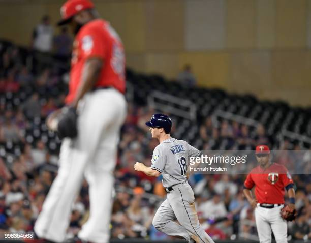 Fernando Rodney and Eduardo Escobar of the Minnesota Twins look on as Joey Wendle of the Tampa Bay Rays rounds the bases after hitting a solo home...