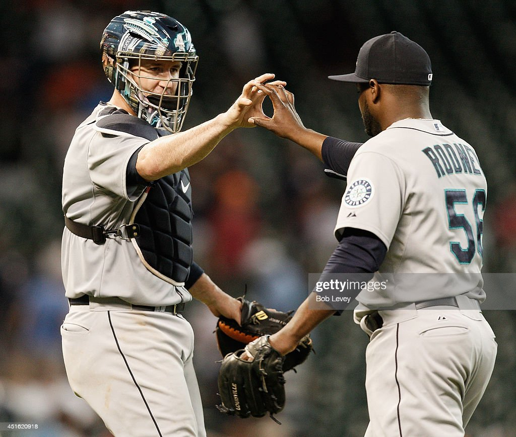 Fernando Rodney #56 of the Seattle Mariners high fives John Buck #4 after the final out as the Seattle Mariners defeated the Houston Astros 5-2 at Minute Maid Park on July 2, 2014 in Houston, Texas.