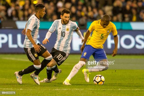 Fernando Roza of the Brazilian National Football Team controls the ball in front of Lionel Messi of the Argentinan National Football Team and Jose...
